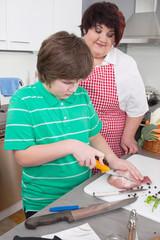 Mutter und Sohn kochen gemeinsam Fleisch