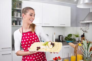 Junge Frau bereitet für eine Party vor - Käseplatte