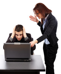 Angry businesswoman showing her emplyee the mistakes on a laptop