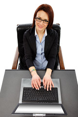 Charming businesswoman with laptop in front, looking up