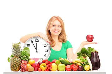 Woman with red apple, clock and fruit and vegetables on a table