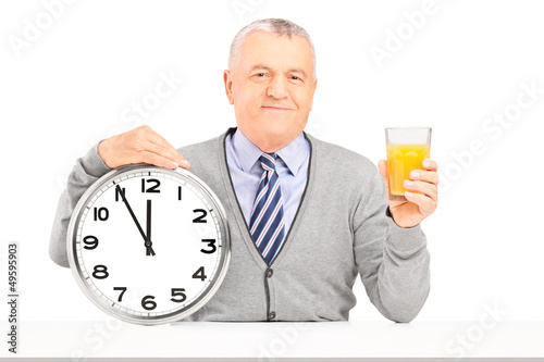 Smiling gentleman sitting and holding a wall clock and glass of