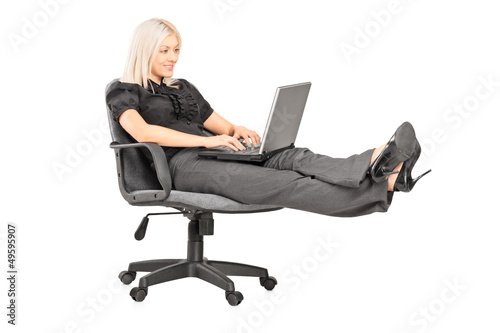 Young woman sitting on office chair with her legs up and working