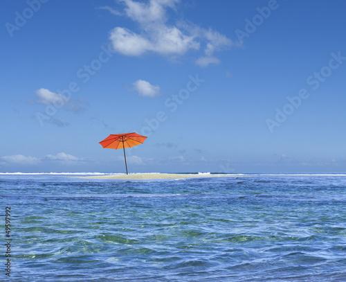 parasol de plage sur îlot de sable blanc