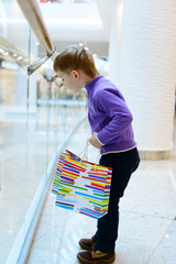 Cute little boy with shopping bags near handrail