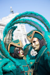 Couple of green carnival masks in Venice, Italy