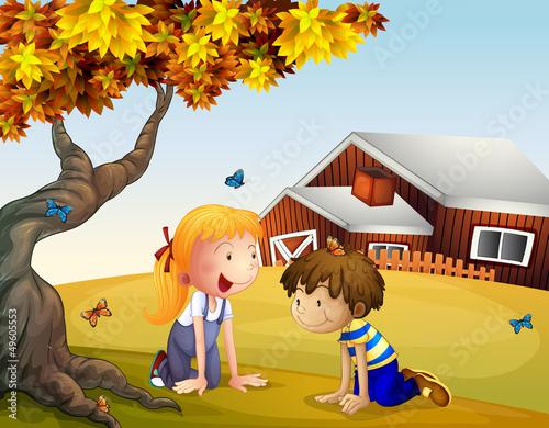 Foto op Canvas Boerderij Kids playing with the butterflies near a big tree