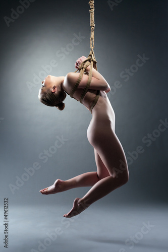 Slim young woman binded with shibari rope
