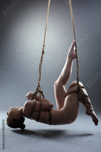 Slim young woman in wire of shibari