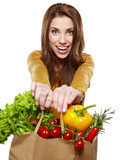 Young woman holding a grocery bag full of fresh and healthy food