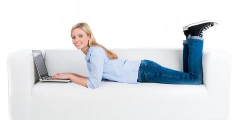 studentin liegt mit dem laptop auf dem sofa