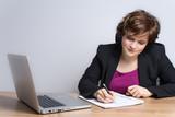 Junge Frau arbeitet am Schreibtisch