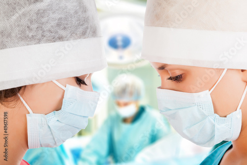 Two female surgeon with nurse in operation room