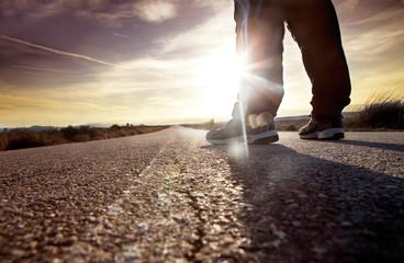 hombre en la carretera y puesta de sol