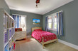 Kids bedroom with red bed and grey walls.
