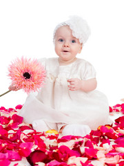 happy baby girl with flower sitting among rose petals