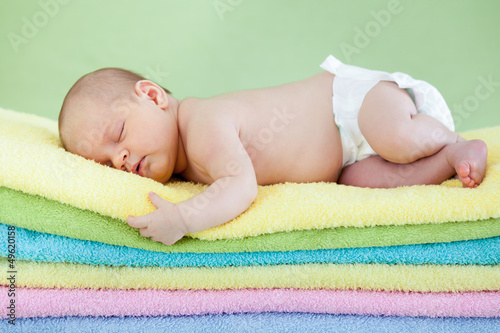 cute baby girl  sleeping on colourful towels