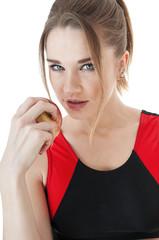 Seductive   athletic  girl   in tracksuit eating a red apple.