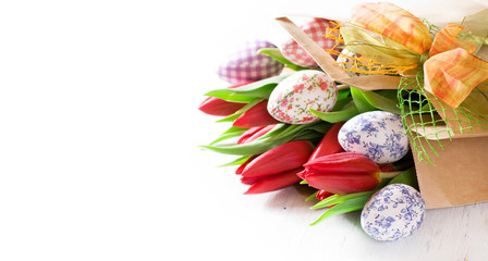 Image of decorative Easter eggs and tulips in brown bag