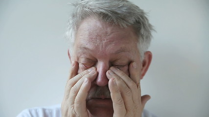 senior man rubs the area around his eyes