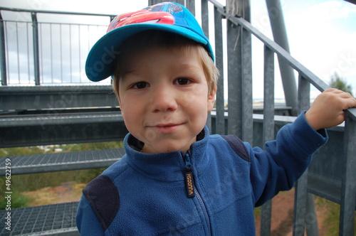 Kind hält sich fest am Geländer