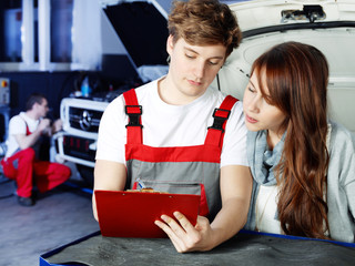 Customer and mechanic in a garage looking at a quotation