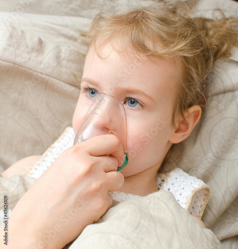 Girl lying in bed with inhalator mask on the face