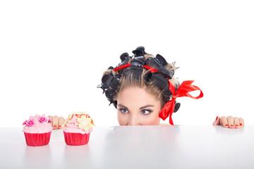 Junge Frau schielt auf Cupcakes im Pinup Style