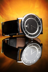 luxury watches with a leather strap on a flame background