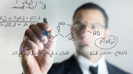 man writing chemical formulas over a transparent screen