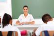 beautiful female primary school teacher sitting in classroom