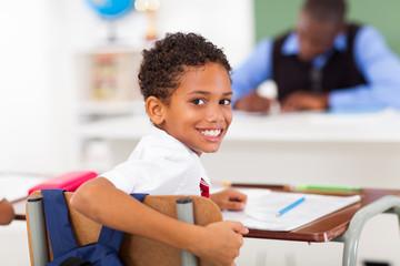 cute elementary schoolboy looking back in classroom