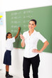 primary maths teacher in front of chalkboard in classroom