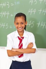 elementary schoolgirl standing in front of  chalkboard