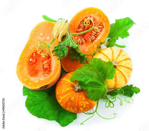 Cut pumpkin with pumpkin seeds and green leaves