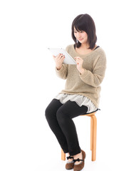a young asian woman using tablet computer