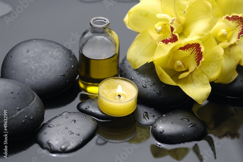 Yellow orchid with candle and massage oil on therapy stones