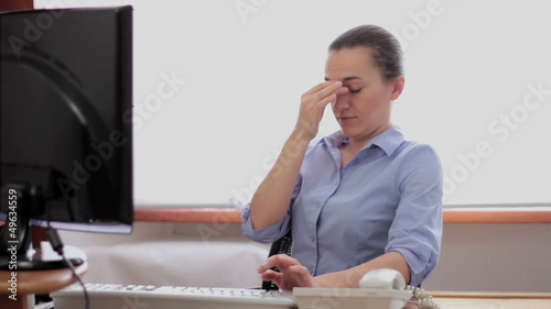 Young business woman with myopia sitting at computer