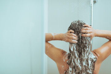Young woman washing head with shampoo. rear view