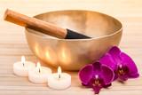 Klangschale mit brennenden Kerzen und Orchideenblüten
