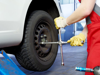 Tightening the wheel nuts with wheel nut wrench to fit a tyre
