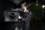 Man looks into viewfinder of a TV Studio Camera
