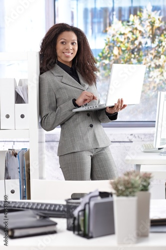 Pretty businesswoman with laptop smiling