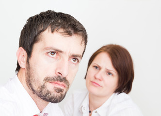 Portrait of upset young couple sitting seperately in the bedroom