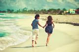 Lovers running along the coastline