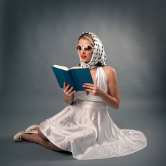 Retro woman with sunglasses reading book portrait