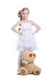 Cute little girl with teddy bear posing in studio
