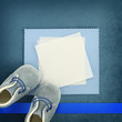 Blank card with baby shoes on blue background
