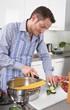 Single Mann kocht daheim in der Küche