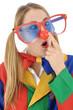 Junge Frau im Clown-Kostüm mit großer Brille